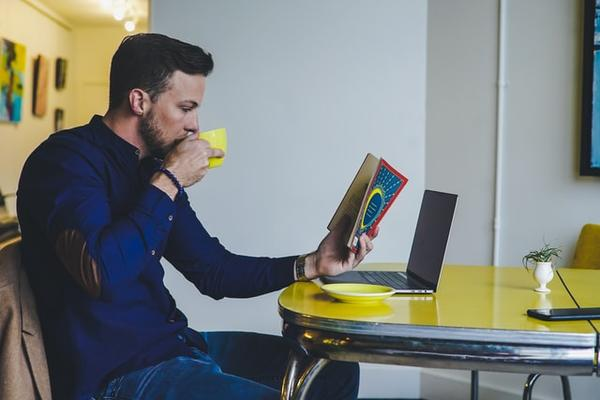 Male student drinking tea and reading a book at home