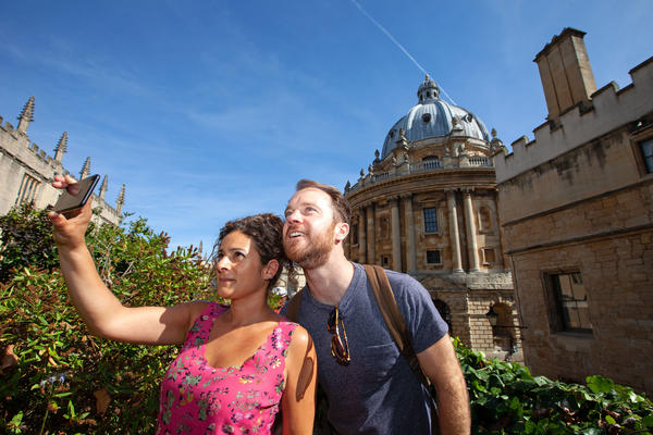 Man and a woman taking a photo together at the Radcliffe Camera