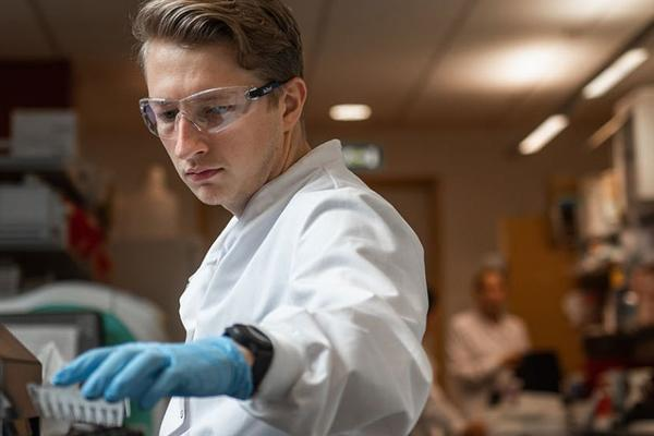 Male researcher wearing goggles and gloves reaching for a palette