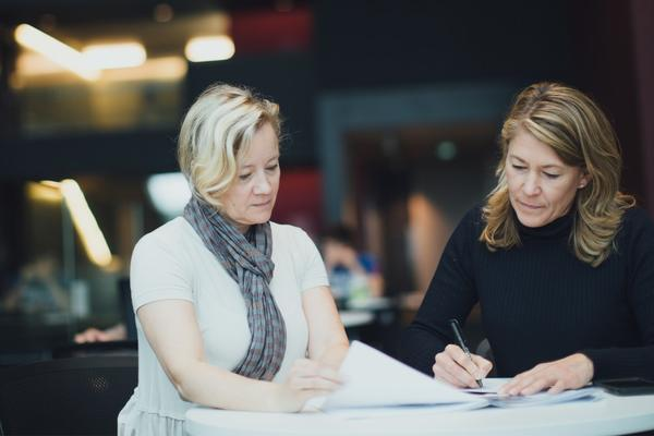 Two female colleagues in a meeting, one writing notes
