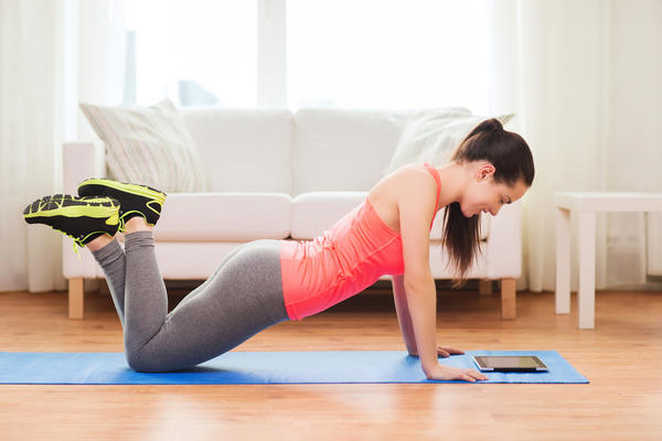 Woman working out at home using an app on her tablet