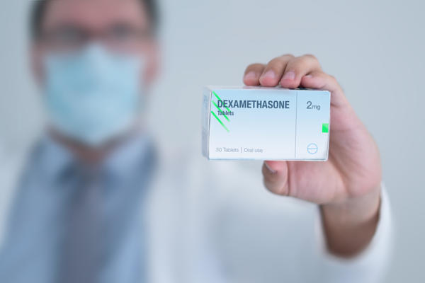 Doctor in a mask holding a box of dexamethasone