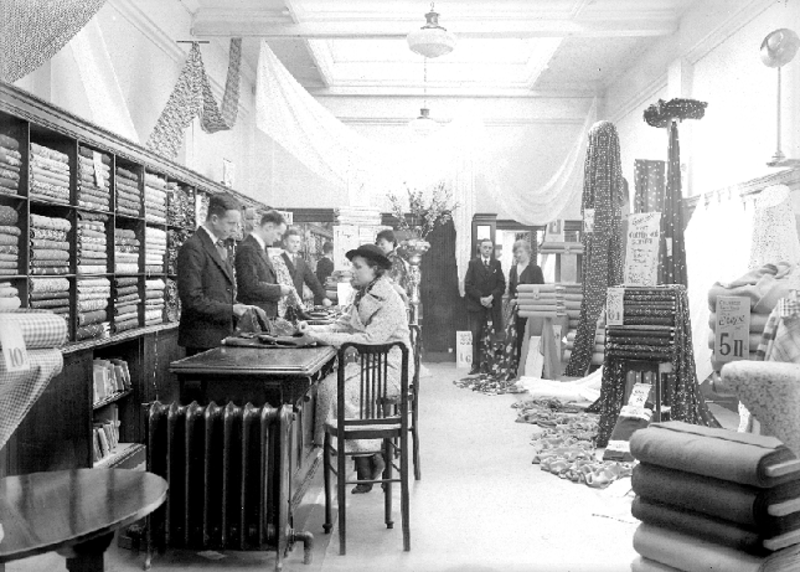 Black and white picture from 1938 showing customers and staff in the fabric department of Charles Babcock's and Co Ltd